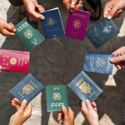 Exchange students holding passports to depict MBA colleges in India with best international tie ups