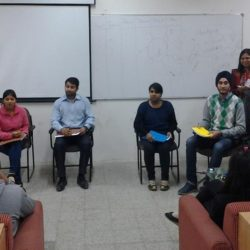 Students taking part in a group discussion which is being moderated by a moderator